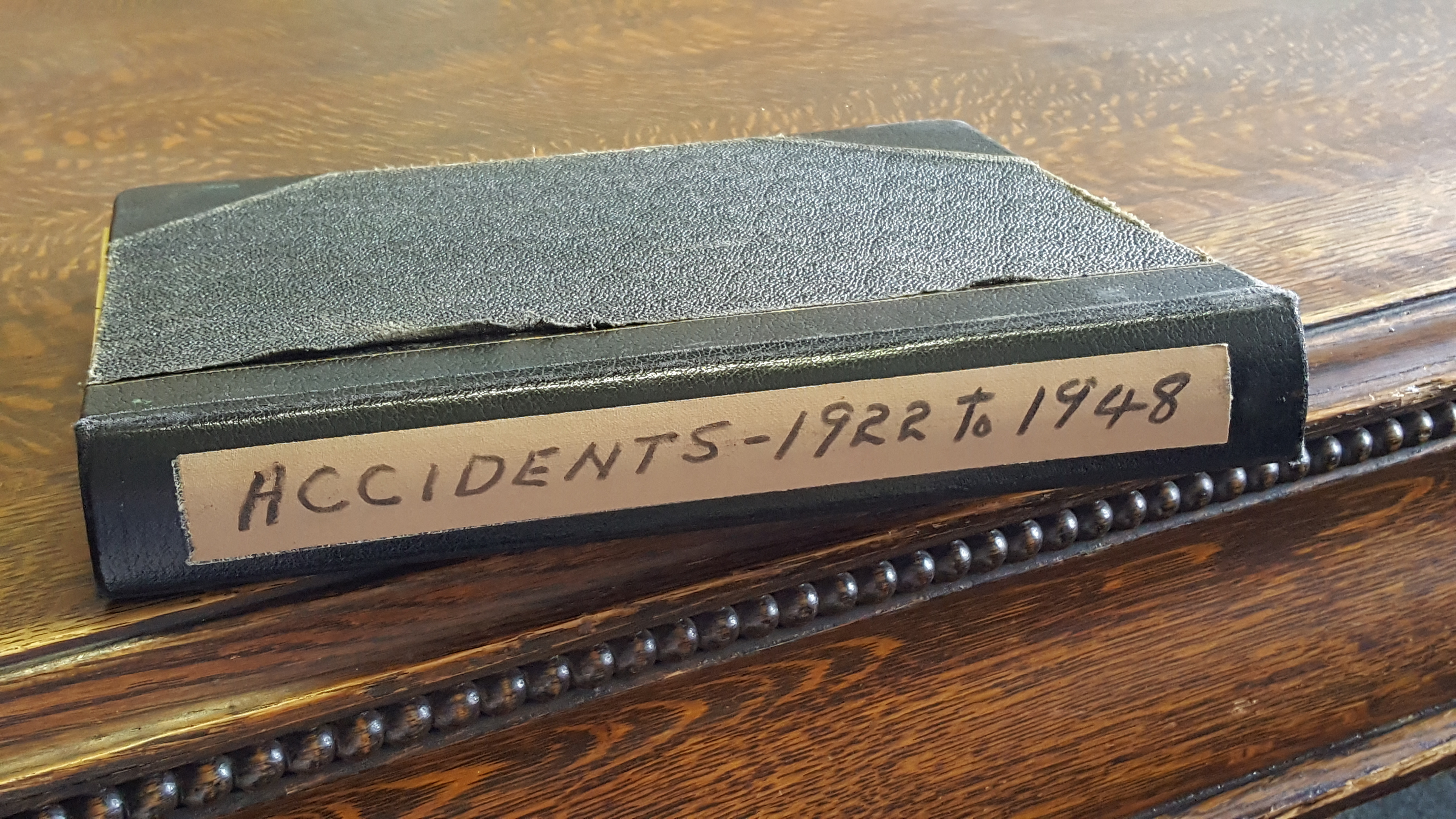 Old black notebook sitting on a wooden table. Tan coloured sticker on the side of the book reads, Accidents - 1922-1948