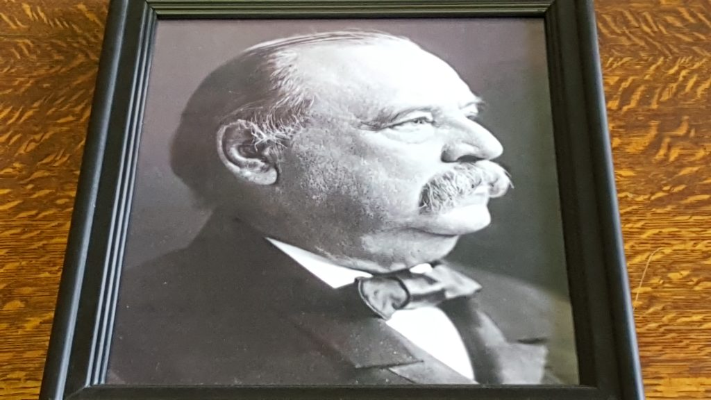 Black and white framed photograph of Francis Clergue. Frame and photograph were placed on a wooden table for this photograph.