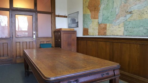Large wooden desk sitting in the middle of a wood panelled room, view is facing in the direction of the door. Large hand painted wall map is pictured on the right.