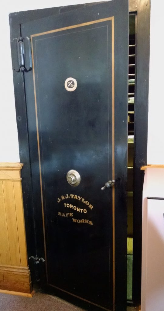 Heavy black metal door of a walk-in safe with a gold painted trim, and J. & J. Taylor, Toronto, Safe Works painted in gold below the combination lock and handle.