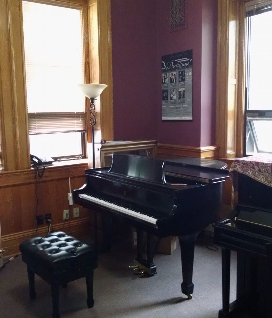 Two pianos and a piano bench side by side in a small room that has several big windows, wood panelling, wooden door frames and base boards, is painted burgundy and is carpeted.