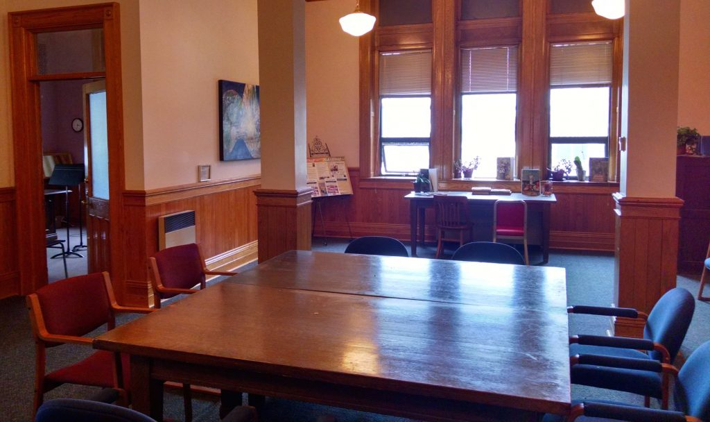 Looking west into the Algoma Conservatory of Music waiting room. View from the door to the room. Big support beams in centre of room. Large window directly to the front. Teaching or office door open on the left of the photograph. Large table and chairs in the centre of the room.