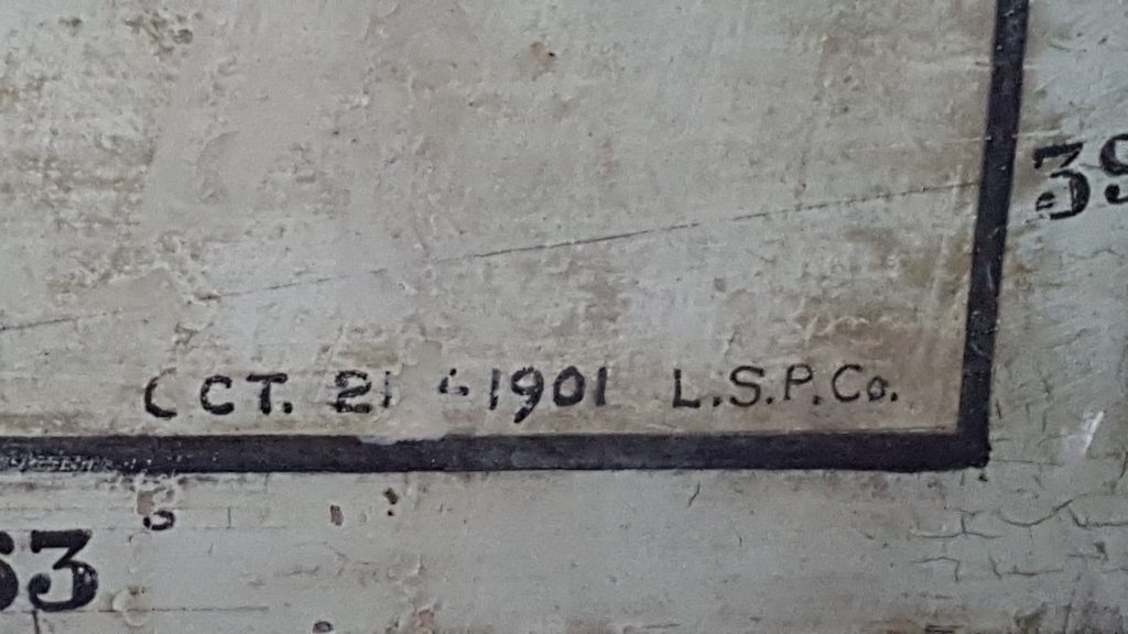 Photograph of the corner of Clergue's wall map. Partial longitude and latitude numbers visible as well as date it was drawn, 1901.
