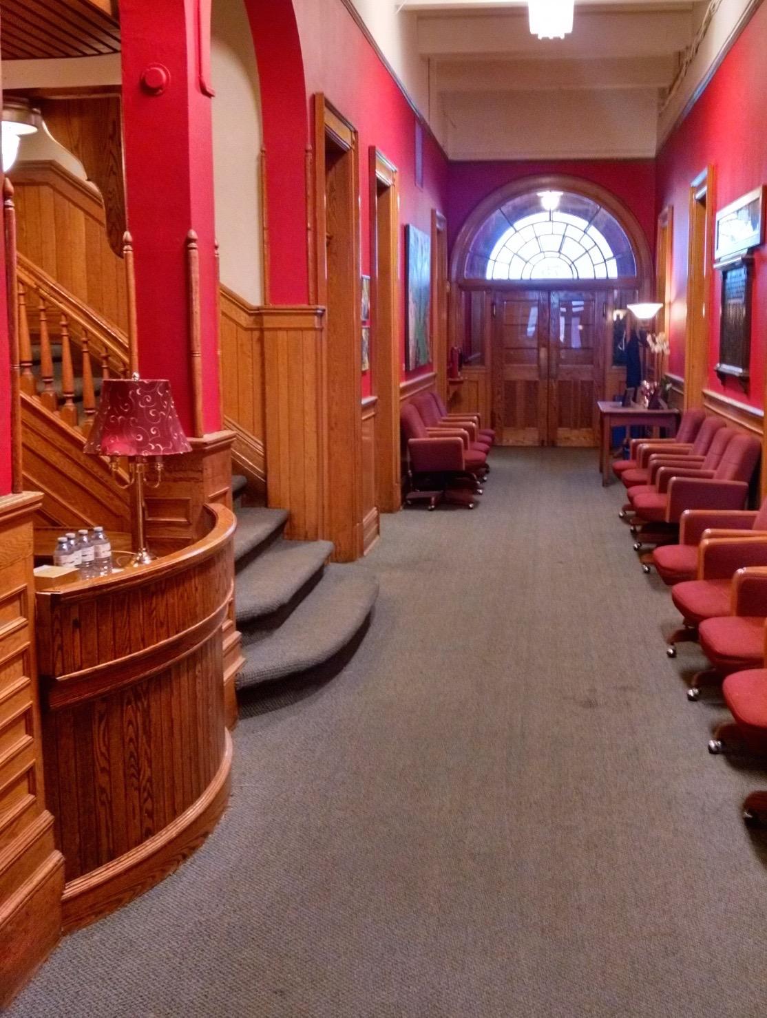 Hall d'entrée et escalier central du Conservatoire. Rangées de chaises alignées de chaque côté du hall d'entrée. Portes françaises et fenêtres au fond du hall.  Détails de l'escalier et du bureau de réception en bois.