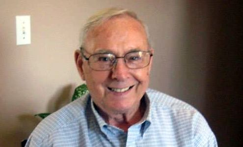 Headshot of retired paper mill worker wearing thin-rimmed glasses and a button-up shirt.