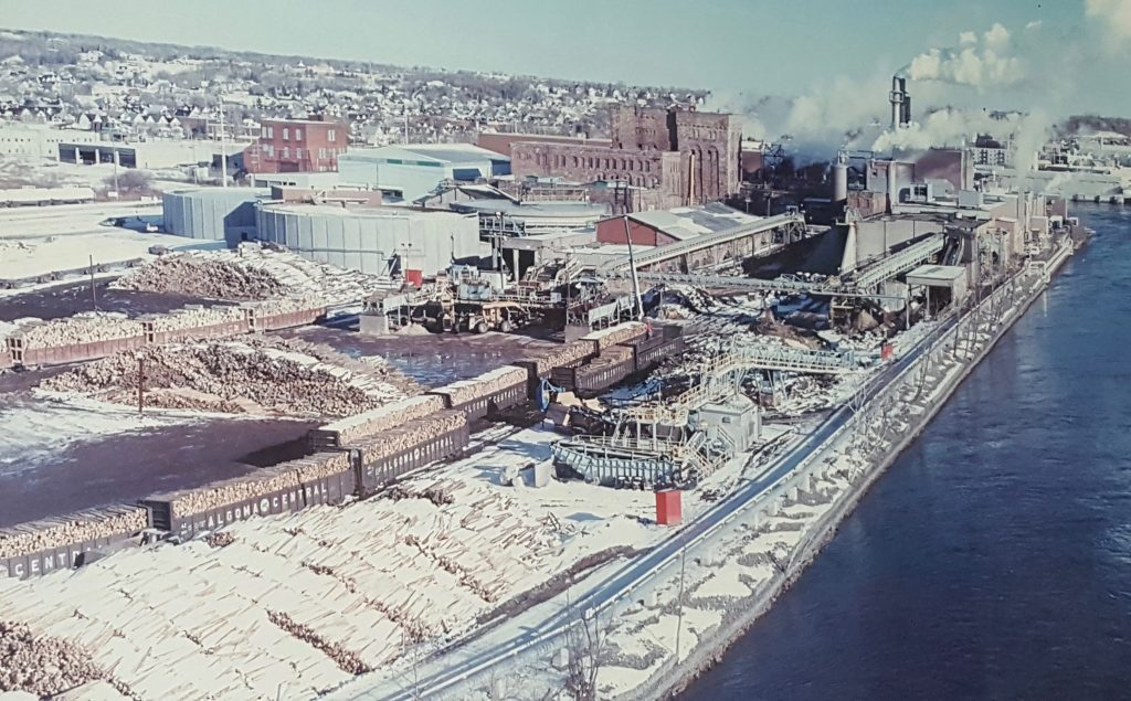 Photo of a framed photograph. Bird's eye view of the paper mill site with buildings, log piles and railway cars