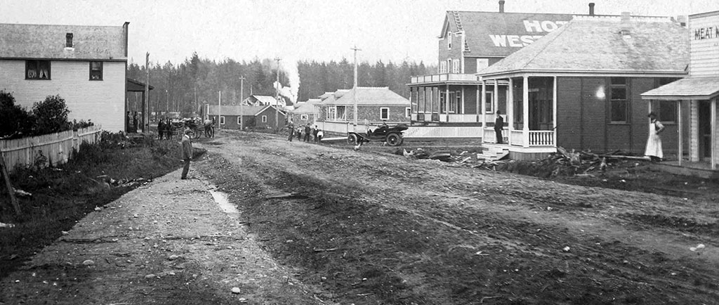 A black and white photograph of a wide dirt road with buildings on both sides of it. There is a person standing outside the entrance of two buildings on the right and a group of people visible down the road near an old automobile.