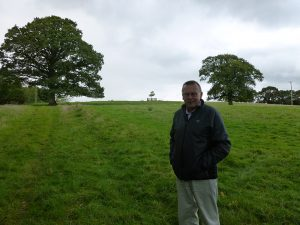 Tom Pope stands in a grass field that has an impression of an old trail in the grass. There are two large trees and a wooden fence visible in the background.