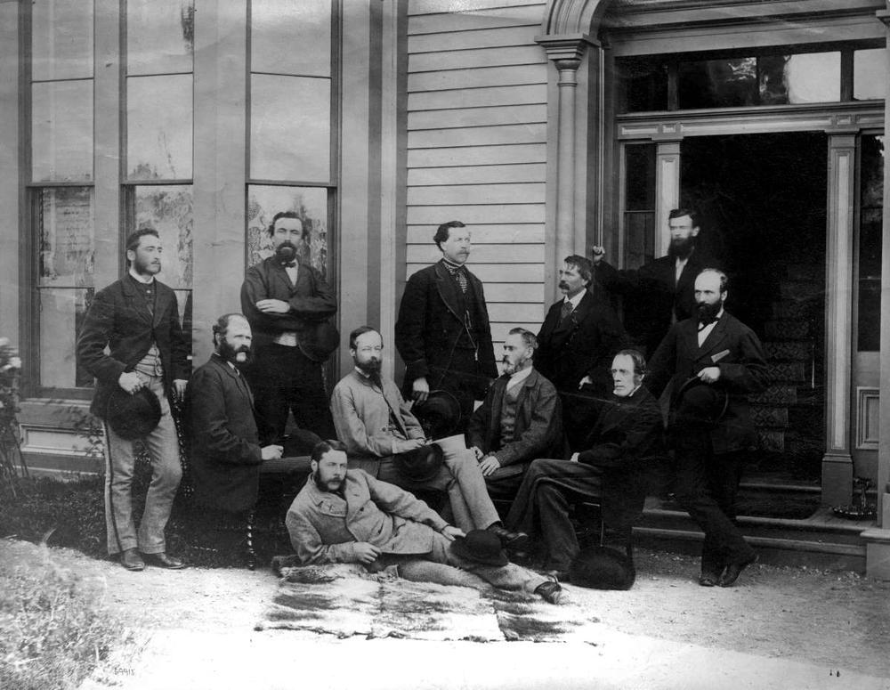 A black and white photograph of Walter Moberly and ten other men of a CPR Survey Party. The men are wearing suits and are organized into three approximate rows in front of a building. One gentlemen is laying on his side in the front row, the second row consists of four seated men, and the third consists of six men standing.