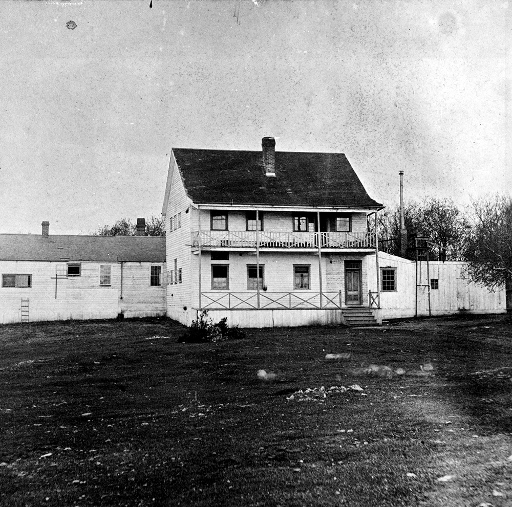 A black and white photograph of the Victoria Lunatic Asylum. The main building is two storeys with a porch on the first level and a deck on second. There is a long one story building directly behind the front building.