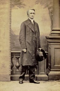 A black and white studio portrait photograph of a Bishop George Hills wearing a long coat. He is holding a top hat in his left hand and has his right hand clenched at his side.