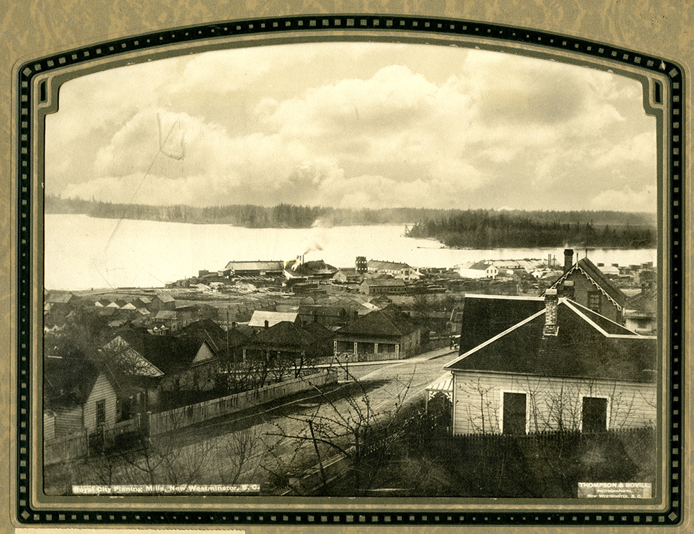 A sepia toned photograph taken from a high perspective of New Westminster that shows a number of houses and the Royal City Planing Mills along the Fraser River.