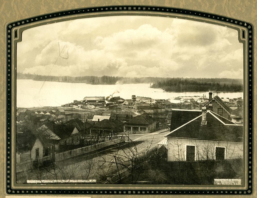 Une photographie monochrome aux tons sépia, prise en plongée, de New Westminster; on y voit l'usine de rabotage appelée Royal City Planing Mills sur la rive du fleuve Fraser.