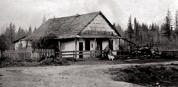 A black and white photograph of the Jackman's first Aldergrove house. The house is light coloured with a wooden shingle roof, a picket fence on the left side, and a wooden fence in front of the house. Jackman and a light coloured dog are standing in front of the house.