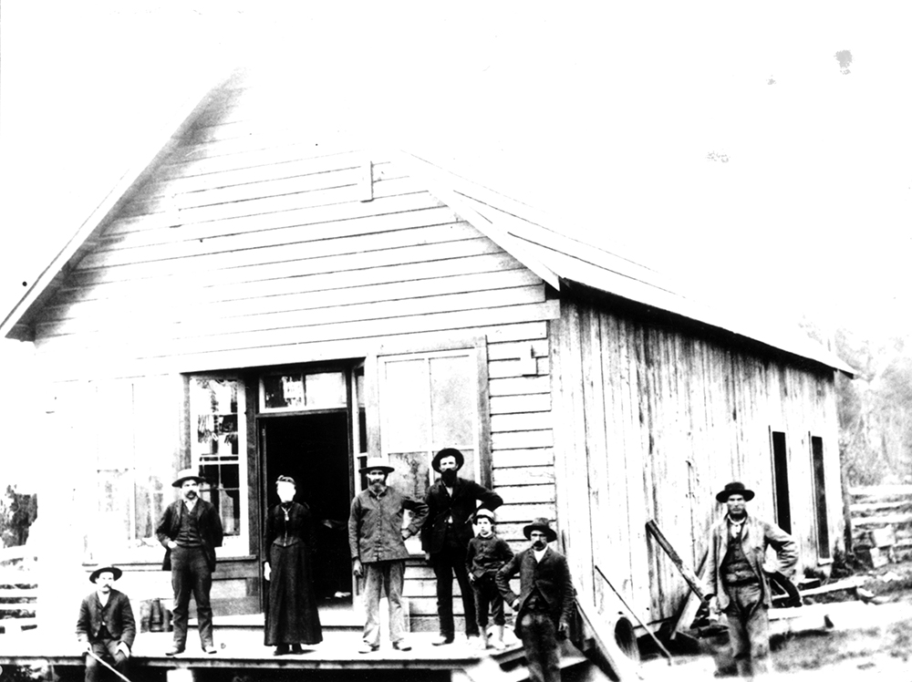 A black and white photograph of six men, one woman, and one boy standing in front of Shortreed's Store. The store is a large wooden building with a front patio that leads to the front door that has a window on each side of it. There are two additional doors visible along the back right side of the building.