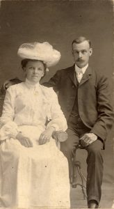 A sepia toned studio portrait photograph of Philip Jackman Junior and Anna Caroline Jackman (née Wadel). The two are seated on separate chairs and Philip has his right arm behind Anna, on the back of her chair. Anna is wearing a white dress and hat and Philip Jr. is wearing a suit.