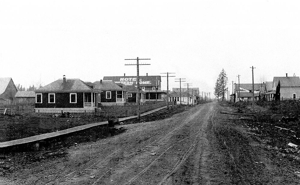 A black and white photograph of downtown Aldergrove circa 1900. A dirt road runs through the small town that has buildings on both sides of the road.