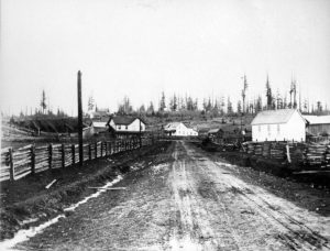 A black and white photograph of Murray's Corners from the Old Yale Road in Langley. The road goes up a hill and is lined with wooden fences on both sides. There are four large buildings at the top of the hill.