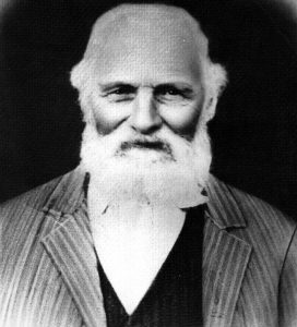 A black and white studio bust portrait of an elderly Philip Jackman with white hair and a beard. Jackman is wearing a striped suit, a dark vest, and a light coloured collared shirt.