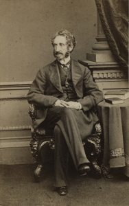 A black and white studio portrait of Sir Edward Bulwer-Lytton sitting on a decorative chair next to a side table with two books on it.