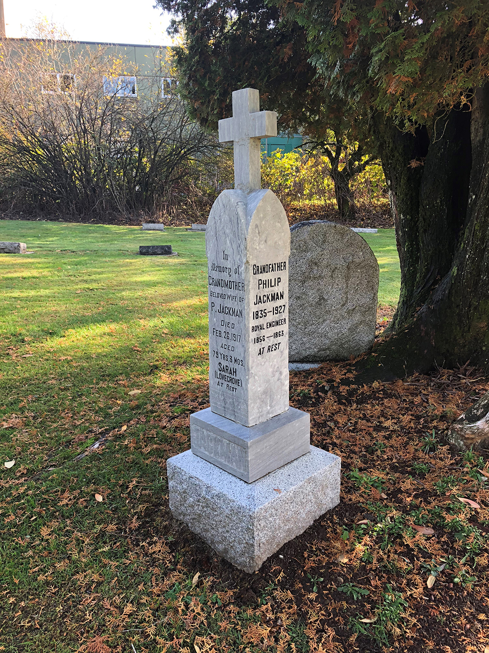 A photograph of a four-sided headstone in a graveyard. The left side of the headstone commemorates the life of Sarah Ann Lovegrove and the right side commemorates Philip Jackman.