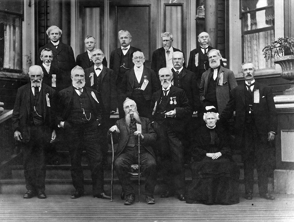 A black and white group photograph of one woman and 15 men formally dressed and organized into three rows. The bottom row includes an elderly Philip Jackman who stands on the left. The first row also includes three men standing and one man and one woman seated. The back two rows consist of five men each standing on steps.