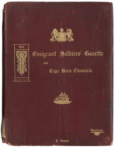 The front cover of a 1907 souvenir edition of The Emigrant Soldiers' Gazette and Cape Horn Chronicle. The cover is burgundy with gold embossed text and images of a ship sailing on water, and the coat of arms of the United Kingdom that contains a lion and a unicorn.