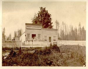 A sepia toned photograph taken circa 1865 of a building with two storefronts. The storefront on the left is a saloon which has a taller false front with a sign on it that reads,