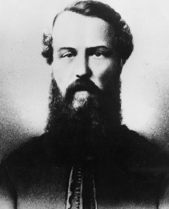 A black and white bust portrait of a bearded Colonel Richard Clement Moody wearing a military jacket.