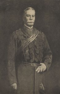 A portrait of Captain James Marshall Grant wearing a formal military outfit. Grant has a sash wrapped around his left shoulder which goes to his right hip. He is wearing a light coloured glove on his left hand which is holding on to his belt and another glove. His right hand is clenched at his side.