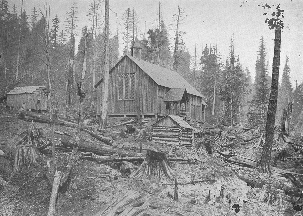 A black and white photograph of the Trinity Church and two other small wooden buildings around it. The buildings are situated in a recently logged plot of land with felled trees and stumps littered throughout the foreground