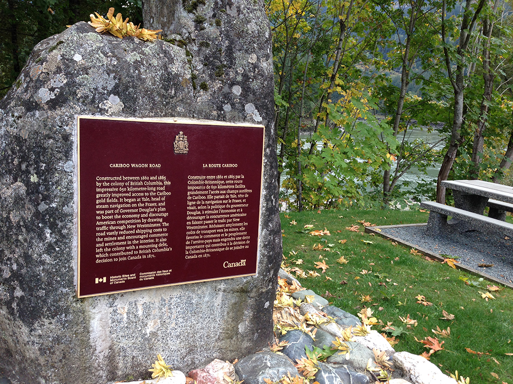 A photograph of a burgundy coloured plaque placed on a large granite stone at Yale, British Columbia. The plaque highlights the history of the construction of the Cariboo Wagon Road.