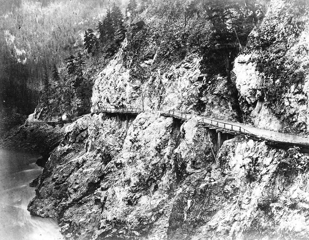 A black and white photograph of a narrow wagon road built along a rocky cliff that sits above a river. Sections of the road are made up of bridges with wooden railings on one side.