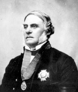A black and white studio portrait photograph of Governor James Douglas wearing a medal around his neck and an ornate badge on the front of his jacket.