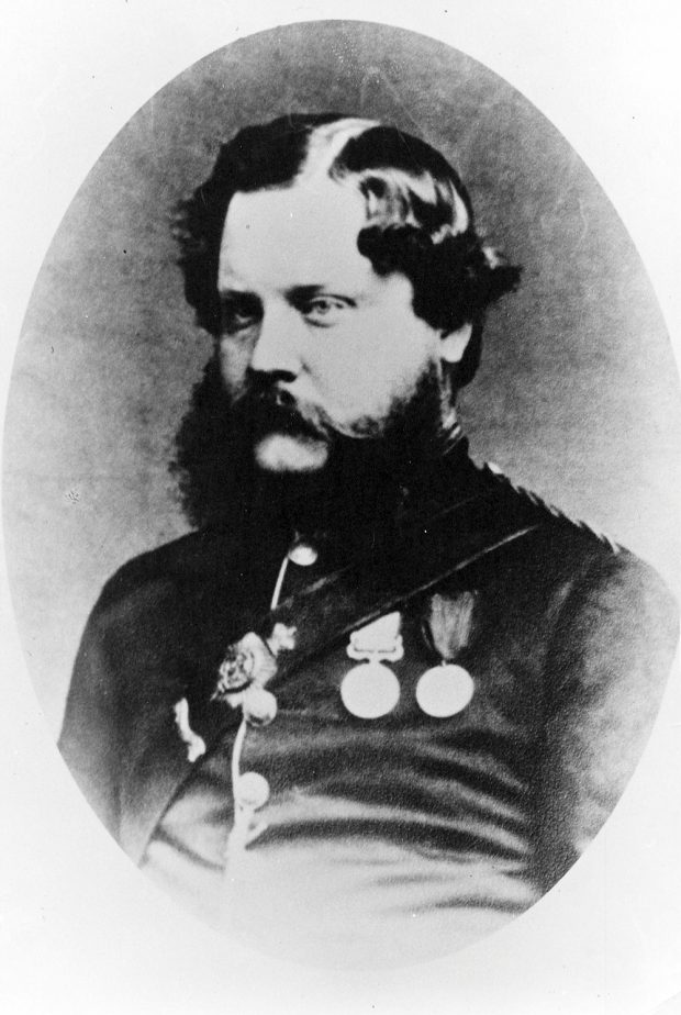 A black and white oval shaped bust portrait of Dr. John Vernon Seddall, dressed in a formal military outfit with an assortment of medals and achievements across his chest. Seddall has slick parted hair and a large beard.