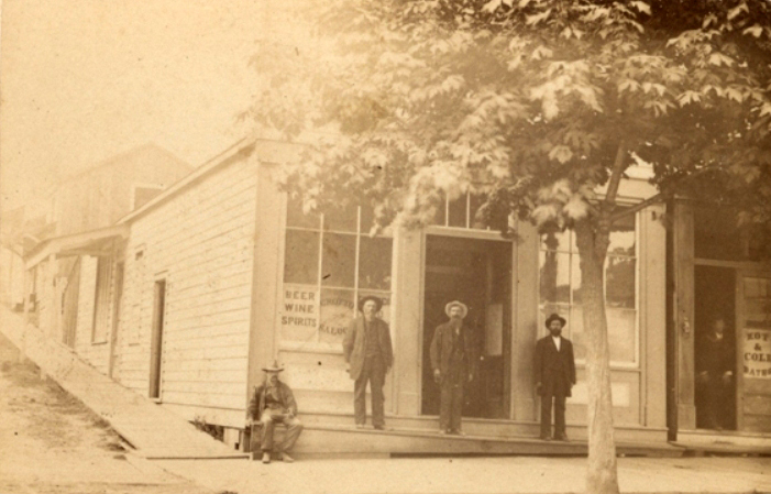 """A photograph of three men standing and one man seated in front of The Grotto Saloon in New Westminster. A sign visible in one of the windows reads, """"Beer Wine Spirits."""""""