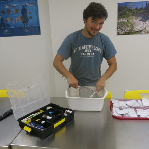 Person cleaning artifacts in a white bin with a toothbrush