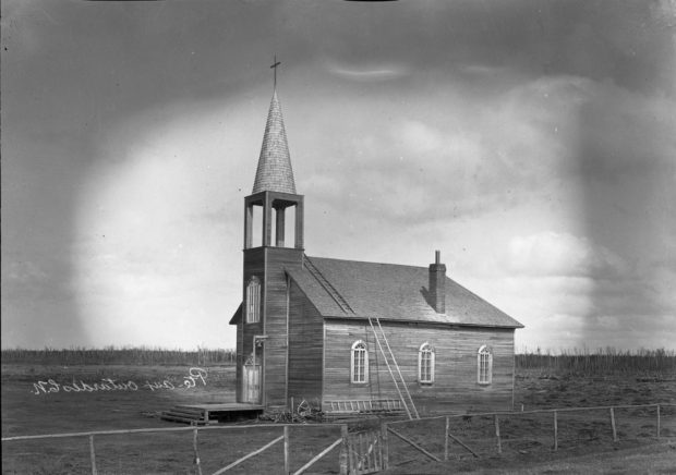 Black and white photo of a wooden church in a plain.