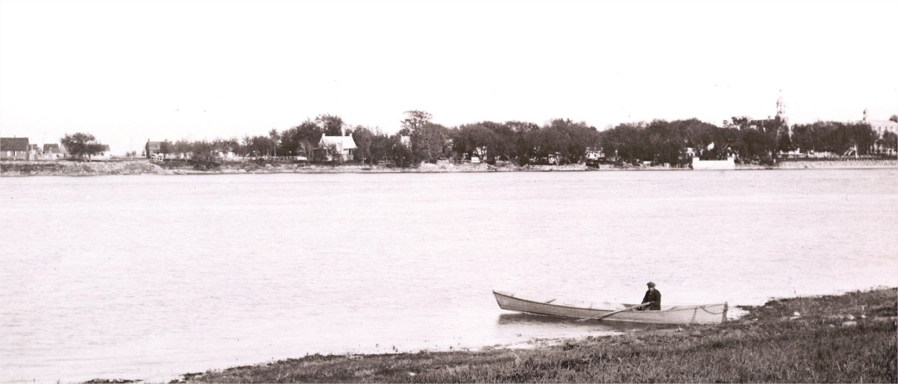 A man in a rowboat with houses in the background
