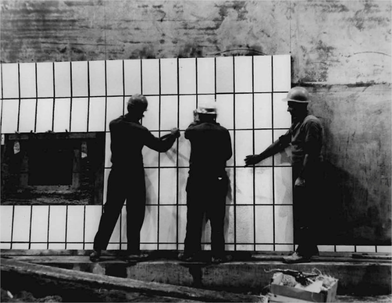 Three men installing ceramic tiling on the wall of a tunnel