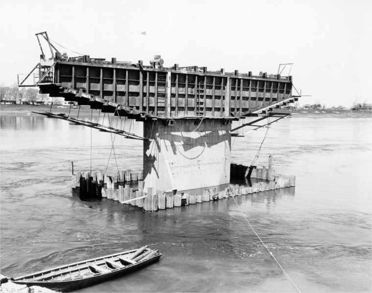 A bridge pillar under construction with a rowboat in the foreground