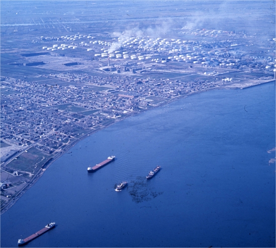 Boats sailing on a river near a city with oil refineries in the background