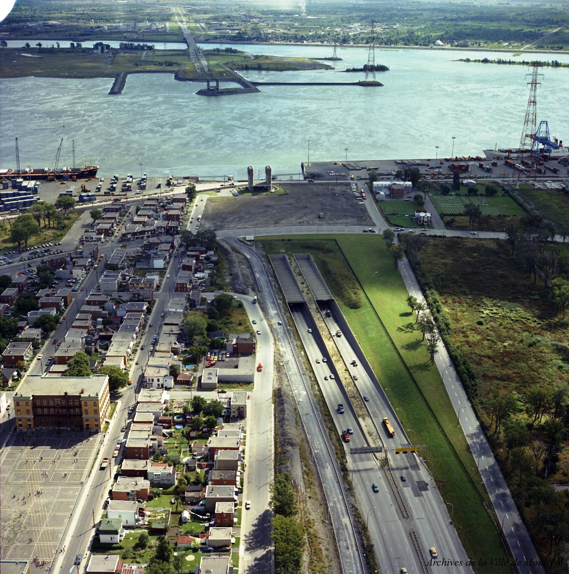 Cars on a highway with a port and a river in the background