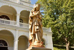 Photographie en couleurs d'une statue dorée de grand format représentant la Vierge Marie. La Vierge porte une couronne et se tient debout sur un dragon, les mains jointes devant elle. La statue est posée sur un socle et, à l'arrière-plan, on aperçoit un bâtiment à plusieurs étages.