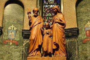 Photographie en couleurs d'une grande sculpture de bois représentant, de gauche à droite, Joseph, Jésus et Marie. La sculpture se trouve sur un socle dans une chapelle sombre et richement décorée.