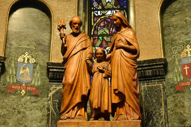 Colour photo of a large wooden sculpture depicting (from left to right) Joseph, Jesus, and Mary. The sculpture is mounted on a pedestal in a dark, ornately decorated chapel.