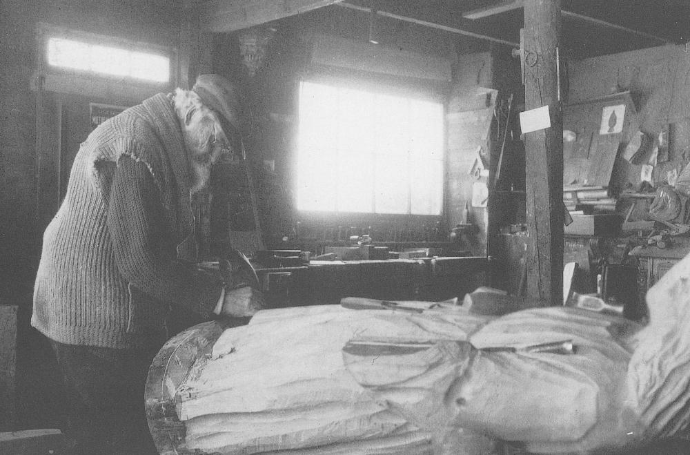 Photographie d'archives en noir et blanc. Un homme sculpte le pied d'une grande statue en bois à l'intérieur d'un atelier où sont éparpillés croquis et outils servant à travailler le bois.