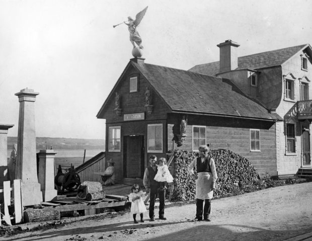 """Black and white archival photo. Two men are seen standing in front of a building consisting of two sections. A sign above the door on the single-storey part on the left reads """"L. JOBIN."""" The two-storey section on the right is the home. The man on the left is accompanied by two young children."""