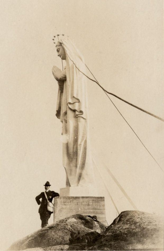 Black and white archival photo. A man leans against the foot of a statue that stands several times his height. The white sculpture of the Virgin Mary has a crown of stars, and her hands are clasped in prayer. The statue is mounted on a pedestal built directly into the rock.