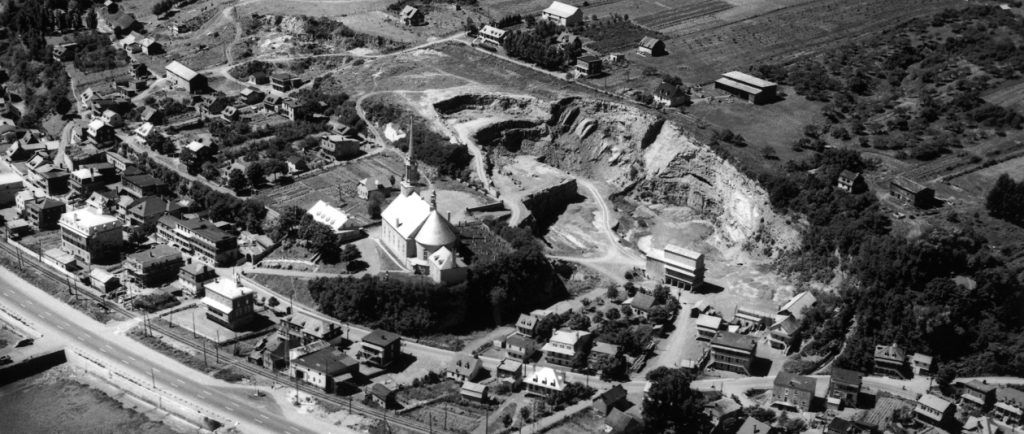 Black and white archival photo. The municipality of Château-Richer radiates around the church, seen in the centre of the picture. In addition to houses, we can see a stone quarry, cultivated fields, a railroad track, and Boulevard Sainte-Anne.